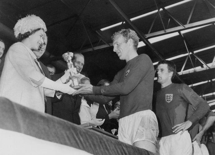 De Britse koningin Elizabeth in 1966 toen ze de wereldbeker (destijds nog de bescheiden Jules Rimet beker) uitreikte aan aanvoerder Bobby Moore van het Engelse elftal. De Engelsen versloegen West-Duitsland in de verlenging met 4-2.