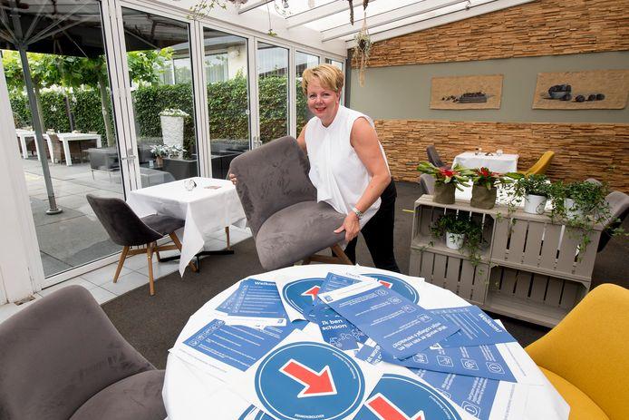 Archieffoto uit juni 2020: Margriet van Heesch, eigenaresse van restaurant De Betuwe, maakt in haar zaak de coronaregels duidelijk.