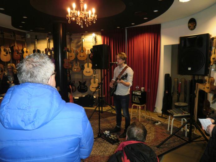 Liedjesschrijver Okke Punt optredend tussen de gitaren van The Guitarfactory.