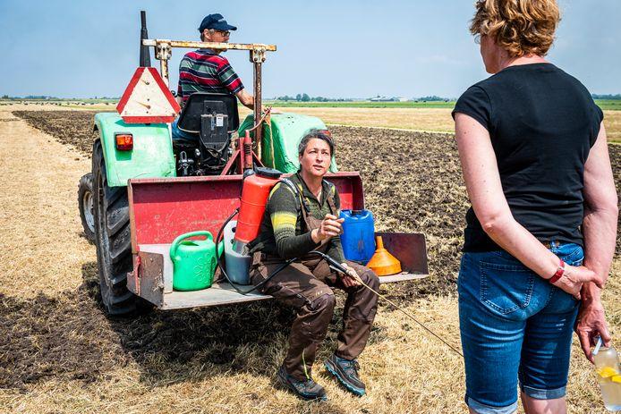 Boeren Isabel Duinisveld (met gele band op de armen) en Reinier de Boo (in de blauwe tractor) bewerken het land samen met de vrijwillers en het eerste zaaigoed wordt geplant.
