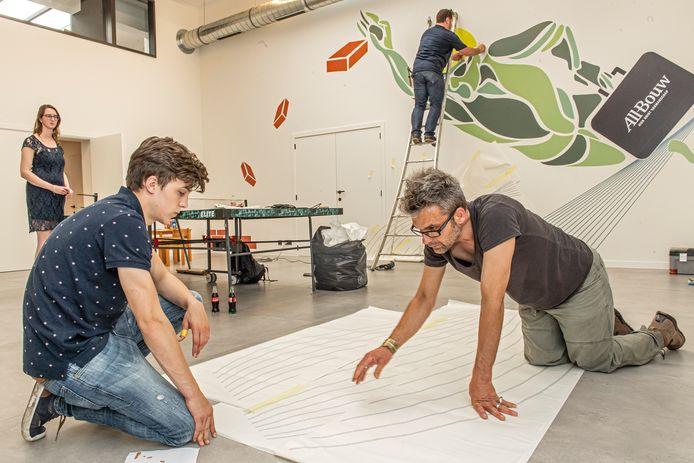 Jesse Buyse en Pieter Demeyer maken de puzzel  in de voorgrond, terwijl leerkracht Ward Desloovere de afbeelding aan de muur bevestigt. Chloë Van Eecke kijkt toe op de achtergrond.