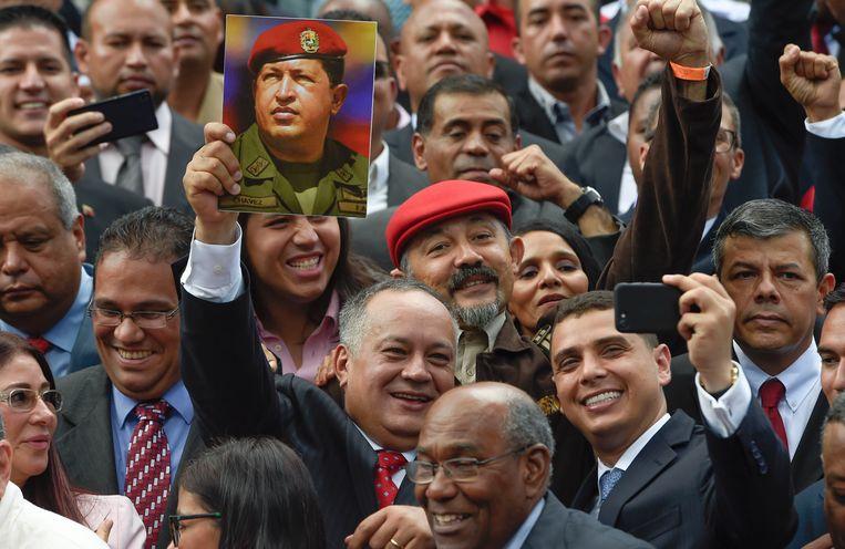 Diosdado Cabello, lid van de grondwetgevende vergadering, houdt na de inauguratie vrijdag een foto omhoog van oud-president Hugo Chávez.   Beeld AFP