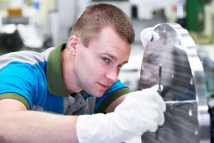 Een werknemer van NTS aan het werk bij het bewerken van metaal.