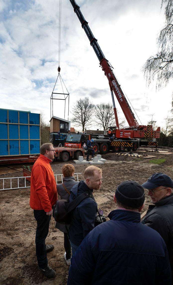 De tiny houses worden op hun plaats getakeld. De actie wordt onder meer gadegeslagen door initiatiefnemer en toekomstig bewoner Johan van Bakel (met oranje jasje).