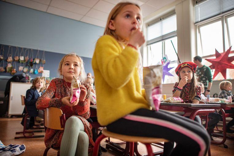 Leerlingen van groep 4 van een basisschool in Abcoude bekijken in december filmpjes over de kerstviering.  Beeld Guus Dubbelman / de Volkskrant