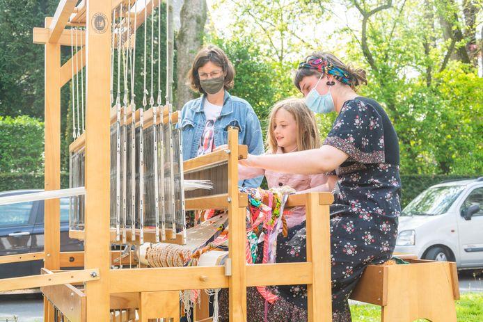 Initiatiefneemster Lisa Debeerst helpt een meisje, aan het handweefgetouw