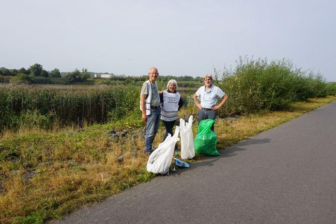 Enkele vrijwilligers, met links Carl Boeckx, kuisen de Rupeloever op.