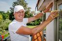 Huisschilder Ruud de Wijs aan het werk: eerst met de hand het raamkozijn schuren.