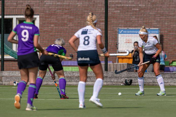 Jannemarije Driessen aan de bal, zus Jolijn (nummer 8) kijkt toe.