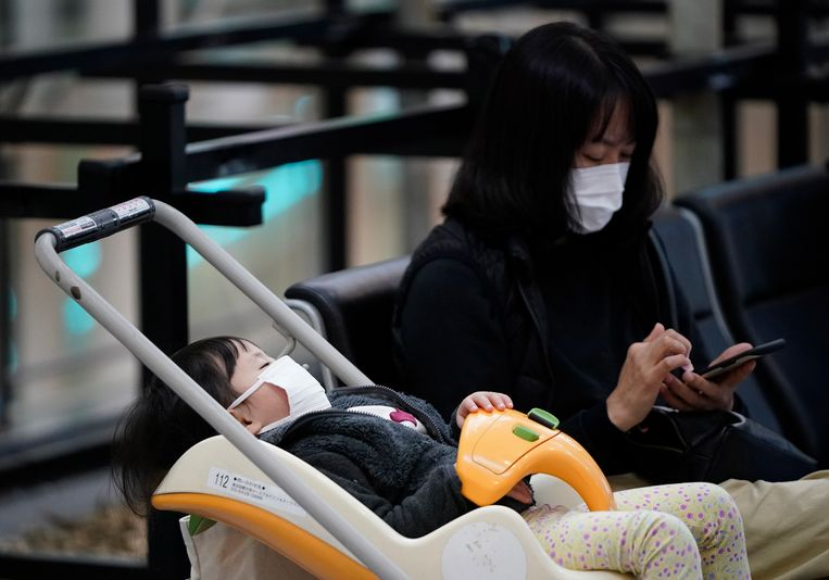 Een moeder met mondkapje op het vliegveld van Tokio in Japan.  Beeld EPA