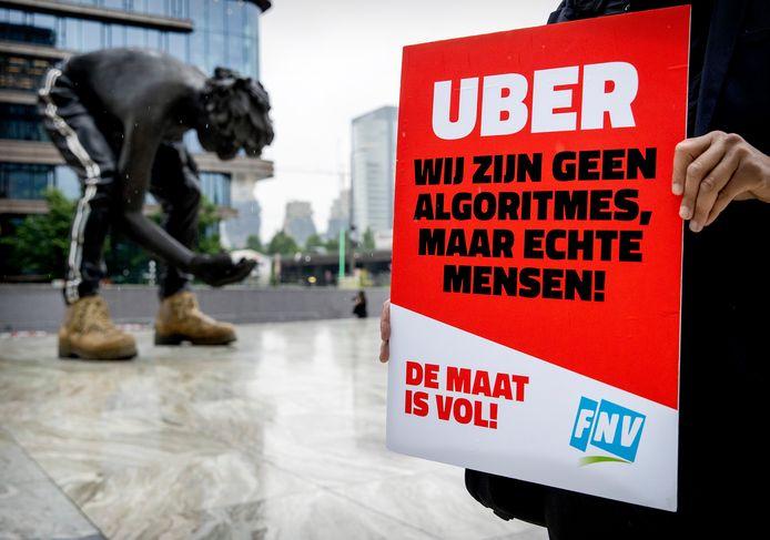 Protestborden van FNV bij aanvang van de rechtszaak in juni tegen Uber over de rechten van chauffeurs.