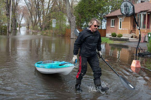 Een man sleept zijn kano achter zich in de overstroomde straten van het stadsdeel Pierrefonds-Roxboro.