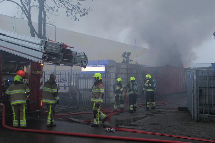 De brandweer in actie bij de brandende container in Millingen.