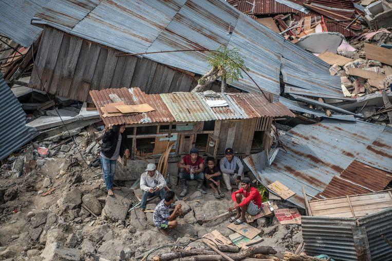 Een groep mannen zit in de schaduw van een verwoest onderkomen. Beeld Getty Images