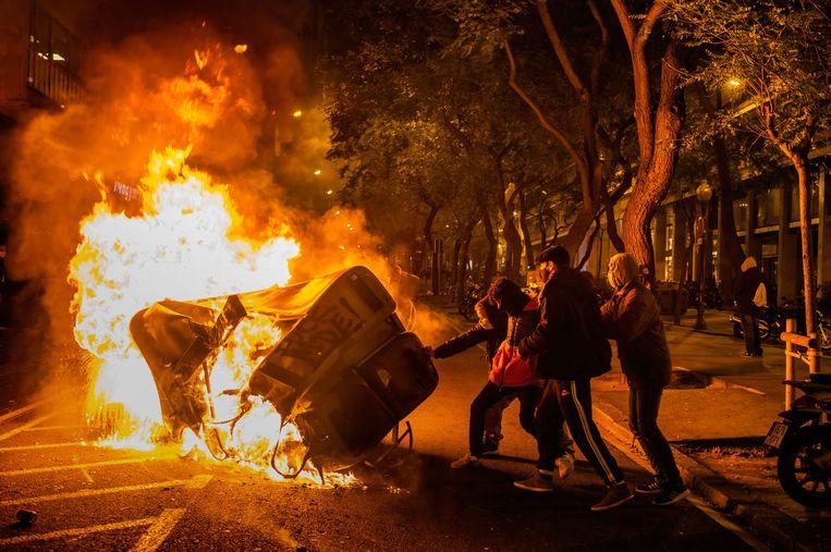 Demonstranten steken vuilniscontainers in brand tijdens protesten in Barcelona.  Beeld Paco Freire/SOPA Images/Shutters