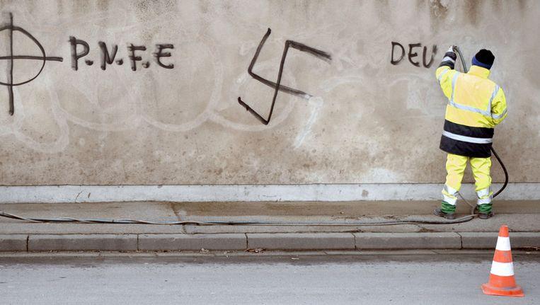 Een gemeentemedewerker verwijdert graffiti in een buitenwijk van de Franse stad Metz. Beeld afp