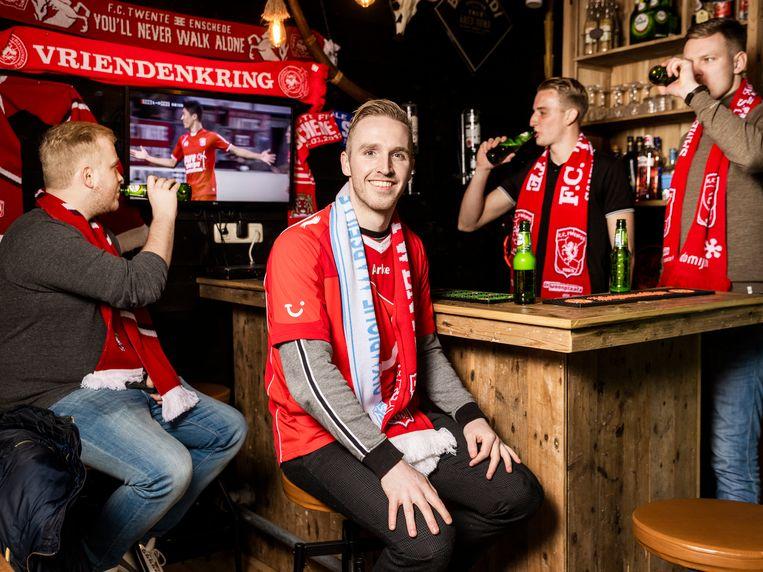 Sergio Westerink kijkt met wat vrienden nu noodgedwongen naar FC Twente in de eigen gemaakte kroeg in de achtertuin. Beeld Jiri Büller