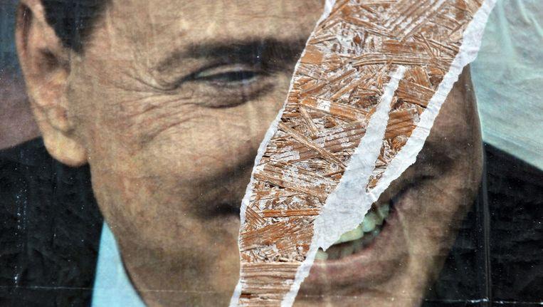 Silvio Berlusconi op een kapotgescheurde verkiezingsposter. Beeld getty