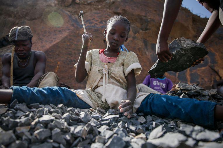 Irene Wanzila van 10 jaar oud breekt stenen met een hamer in Nairobi, Kenia, op 29 september 2020. Volgens de VN heeft de coronapandemie aanzienlijke gevolgen voor de strijd tegen kinderarbeid.  Beeld AP