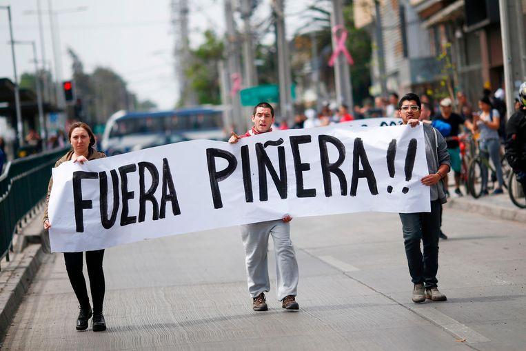 Demonstranten met een spandoek met de tekst 'Pinera buiten' in Santiago.