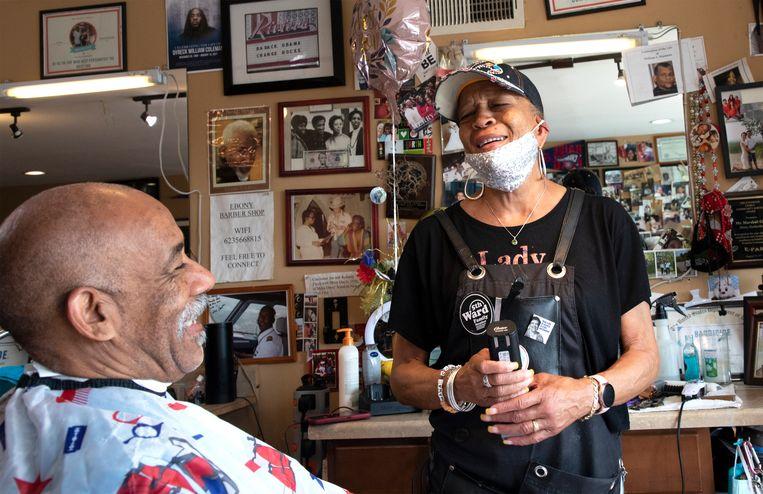 De kapperszaak van Gigi Giles (rechts), Ebony Barbershop, bestaat al meer dan een halve eeuw en vormt het hart van de buurt. Beeld Sarah Hoskins