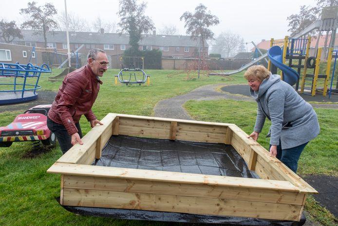 Wim Boone en Els Dekker bezig met de nieuwe zandbak in 't Zand . foto dirk-jan gjeltema