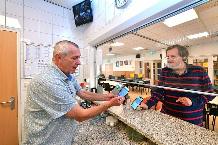 Zo zal het vanaf morgen gaan als mensen - zoals hier in wijkgebouw Ut Praotuis in Etten-Leur - een kopje koffie bestellen dat ze binnen op willen drinken. Voorzitter Louis Boumeester (links) of een van de andere vrijwilligers kan dan vragen om de CoronaCheck te tonen.