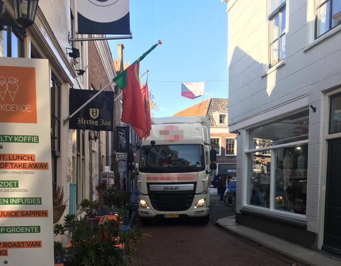 Een vrachtwagen manoeuvreert zich over de Melkmarkt in Zierikzee. De vlaggenmasten aan de gevels sneuvelen daarbij nogal eens.