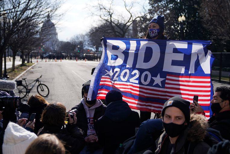 Supporters van Joe Biden vieren de eedaflegging nabij het Capitool in Washington.Om veiligheidsredenen werd het publiek op een afstand gehouden. Beeld AP