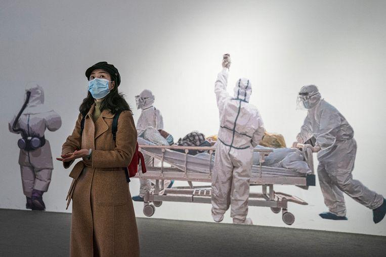 Een vrouw draagt een gezichtsmasker terwijl ze een tentoonstelling in Wuhan bezoekt over de strijd van de stad tegen het coronavirus. Beeld Getty Images