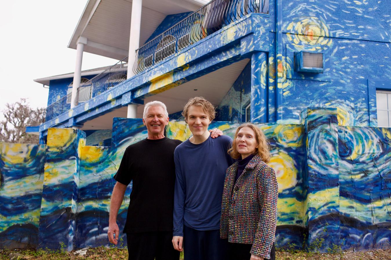 Lubomir Jastrzebski (l) en Nancy Nembhauser (r) met hun autistische zoon voor hun tot kunstwerk omgetoverde huis met de muurschildering van De Sterrennacht van Van Gogh.