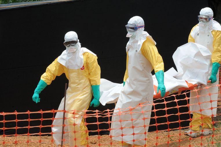 Medewerkers van Artsen zonder Grenzen vervoeren het lichaam van een persoon die is bezweken aan de gevolgen van het ebolavirus, Guinea. Beeld AFP
