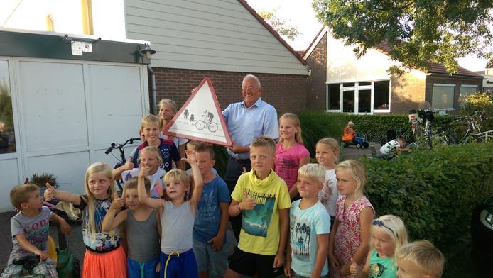 Wethouder Bob Bergkamp en een aantal leerlingen met het nieuwe verkeersbord.