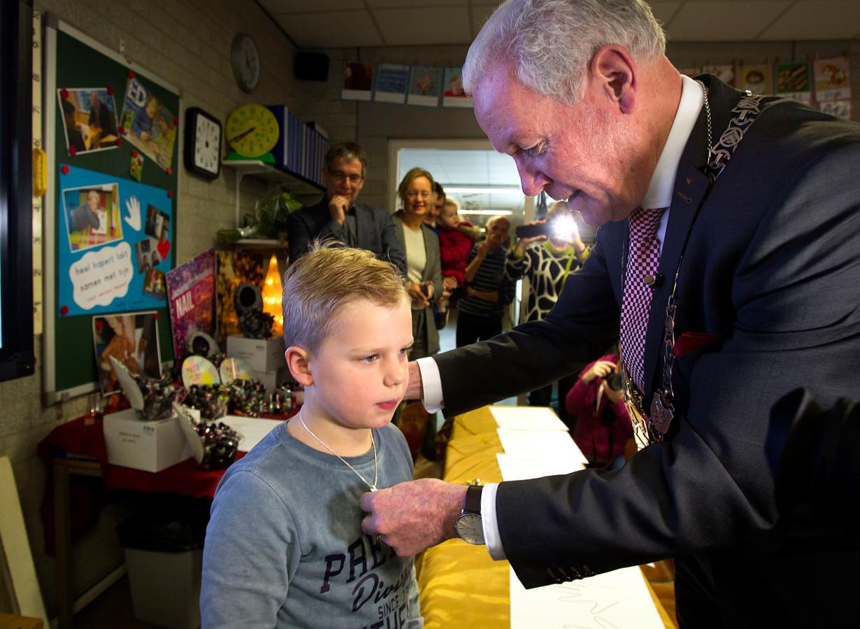 Tijn ontving een kinderlintje van burgemeester Maas.