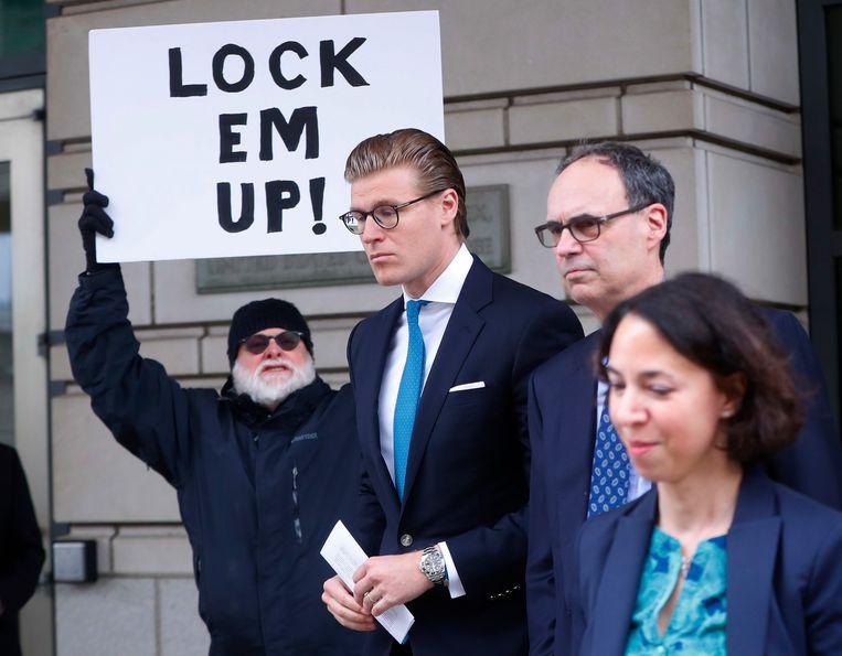 Alex van der Zwaan (tweede van links) verlaat de rechtbank in Washington D.C., met op de achtergrond een demonstrant. Beeld AP