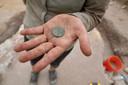 Een archeoloog toont een munt die is gevonden bij de overblijfselen van een slaafgemaakte man op Sint Eustatius.