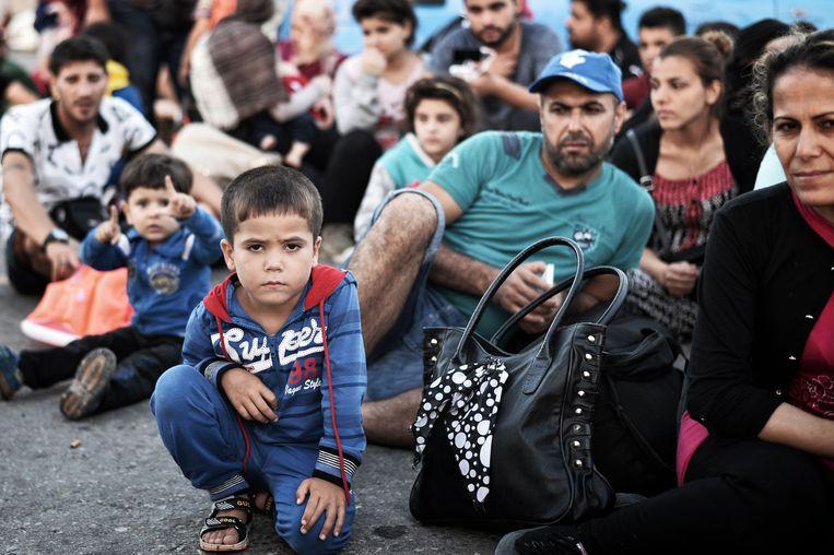 Nieuw gearriveerde Syriërs wachten in de haven van Kos op hun registratie Beeld AFP