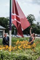 Duiven-burgemeester Huub Hieltjes hijst de nieuwe vlag op het gemeentehuis. Ontwerpster Sanne Smits helpt een handje.