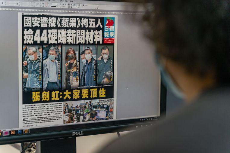 Redacteur van de Apple Daily met op zijn monitor de voorpagina van de vrijdagkrant, met daarop de afbeeldingen van de vijf gearresteerde leidinggevenden. Beeld Getty Images