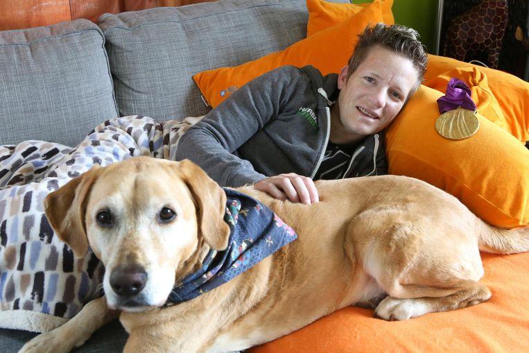 Wielemie met hond Zenn en haar gouden medaille die ze op de Paralympische Spelen in 2012 won.