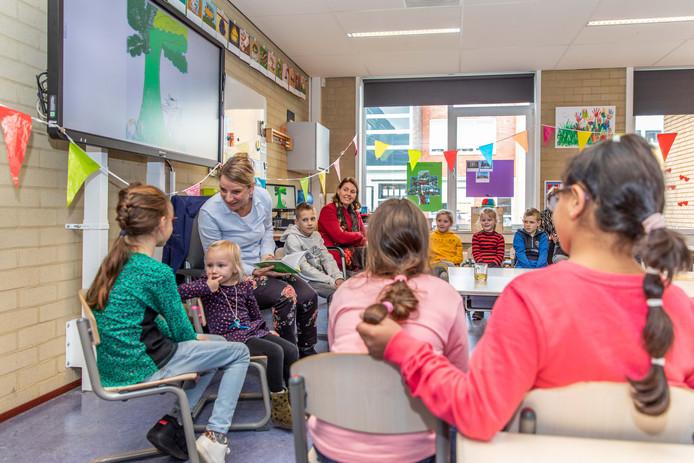 Ingrid van den Broek (derde van links) leest op De Parelmoer in Yerseke voor uit haar kinderboek 'Het geheim van Sophie'. Burgemeester José van Egmond (vijfde van links) luistert mee en krijgt later het eerste exemplaar.