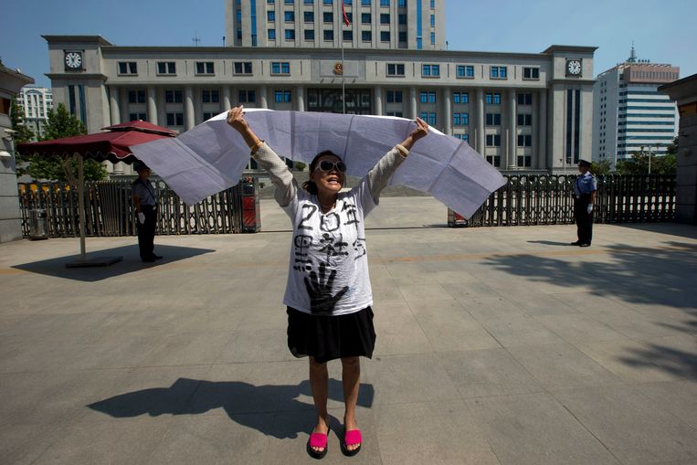 A Chinese woman protests outside the Jinan Intermediate People's Court in Jinan, eastern China's Shandong province Wednesday, Aug. 21, 2013. Former Chinese politician Bo Xilai will stand trial at the court on Thursday on charges of corruption and abuse of power. Individual protestors have turned up at the court hoping to take advantage of media attention around Bo's trial to air their own grievances about China's legal system.  The Chinese characters on her shirt reads