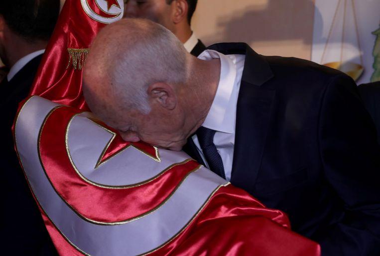 De nieuwe president van Tunesië Kaïs Saïed kust de Tunesische vlag na het bekend worden van de voorlopige verkiezingsuitslag. Beeld null