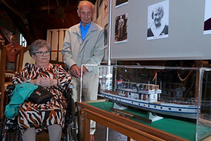 Joost Holster en Dirry van Ooijen-Smits bij het houten scheepsmodel van de Janihudi 4, de veerboot waarop zij zaten die tijdens de Tweede Wereldoorlog door jachtvliegtuigen onder vuur werd genomen bij de oversteek van Gorinchem naar Woudrichem.