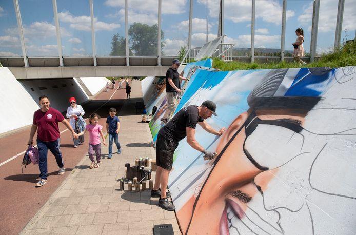 Caspar Caspar van Adrichem (op de voorgrond) en André Merlijn brengen graffiti aan op de wanden van de fietstunnel onder de Rondweg-Oost.
