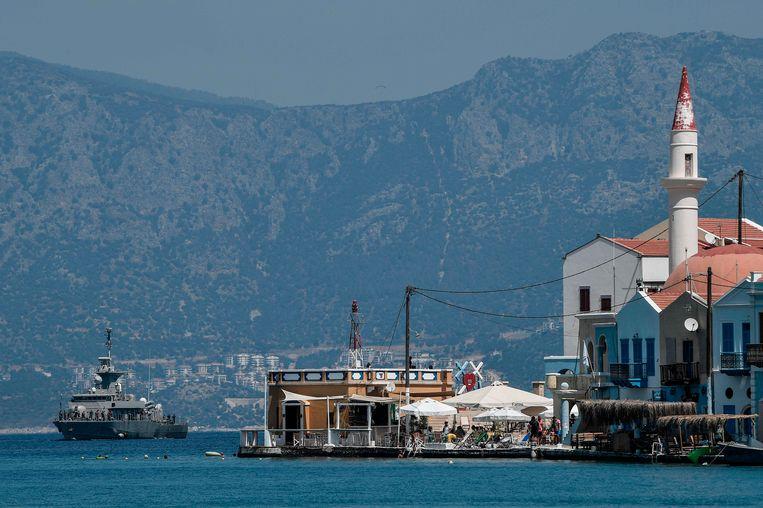 Een Grieks marineschip  ligt voor het eiland Kastellorizo, dat vlak aan de Turkse kust ligt.  Beeld AFP