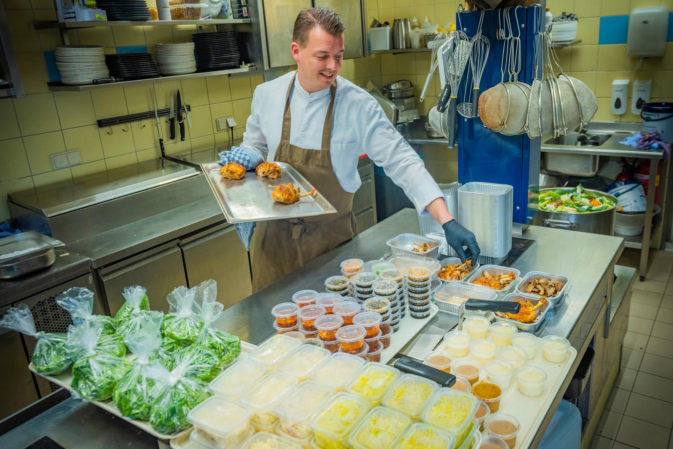 Chef-kok Dennis Bruinzeel van restaurant Hoeve Kromwijk legt zijn culinaire creaties in plastic bakjes.