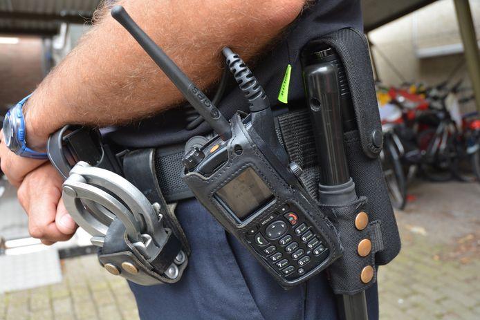De koppel van de politieman op straat hangt vol met uitrusting die in de auto in rug- en bilspieren drukken.