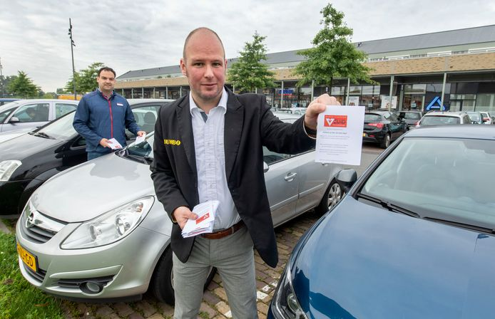Supermarktmanagers Dennis Oude Alink (rechts) en Jan-Willem Vrieze plaatsen dinsdagochtend flyers onder de ruitenwissers van auto's op de parkeerplaats van winkelcentrum Hart van Zuid.
