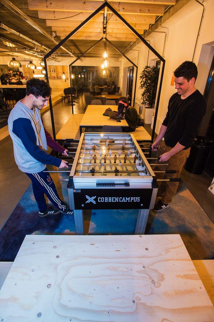 Danny Busel (links) en Gustavo Hering spelen een potje tafelvoetbal in de gemeenschappelijke ruimte van de CobbenCampus.